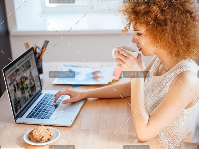 demo-attachment-410-woman-photographer-drinking-coffee-and-working-PJNBP6U